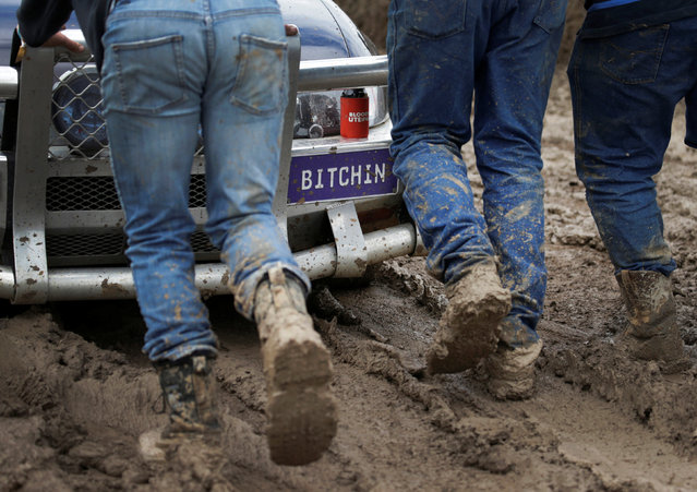 """Volunteers push a bogged Australian ute out of the mud during the """"circle work"""" competition at the Deni Ute Muster in Deniliquin, New South Wales, Australia, October 1, 2016. (Photo by Jason Reed/Reuters)"""