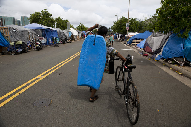 In this Monday, August 24, 2015 photo, Lohe Akau, a 55-year-old homeless construction worker, carries his bodyboard through a homeless encampment in the Kakaako district of Honolulu. There are estimated 7,620 homeless people living on the streets in Hawaii. (Photo by Jae C. Hong/AP Photo)