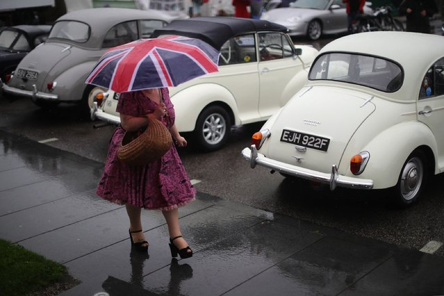 A woman in vintage clothing takes a stroll in the rain past classic Morris Minor cars during Vintage By The Sea on September 3, 2016 in Morecambe, England. Vintage By The Sea is a celebration of 20th century design, fashion and entertainment. Now in it's fourth year Vintage By The Sea is hosted in the seaside resort of  Morecambe. The centre piece of the vintage festival is the fully restored art-deco Midland Hotel where dancing and afternoon tea is served period style. (Photo by Christopher Furlong/Getty Images)