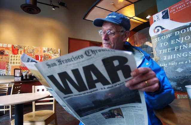 Ray Jacques reads the San Francisco Chronicle's war special section inside a Starbucks coffee shop in San Francisco, in this March 20, 2003 file photo. (Photo by Marcio Jose Sanchez/AP Photo)