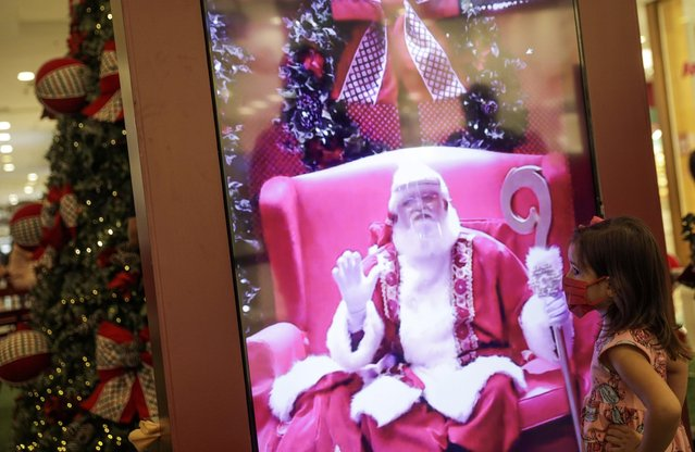 "A child interacts by video with a man who goes by ""Santa Claus Edi Noel"" at NorteShopping mall amid the coronavirus disease (COVID-19) outbreak, in Rio de Janeiro, Brazil, November 13, 2020. (Photo by Ricardo Moraes/Reuters)"