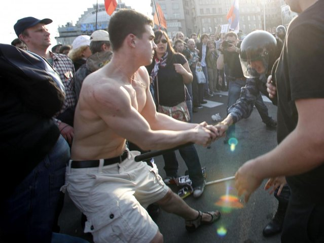 In this photo taken Sunday, May 6, 2012, Denis Lutskevich, left, is detained by police during an opposition rally in Bolotnaya Square in Moscow. (AP Photo/Pavel Golovkin)