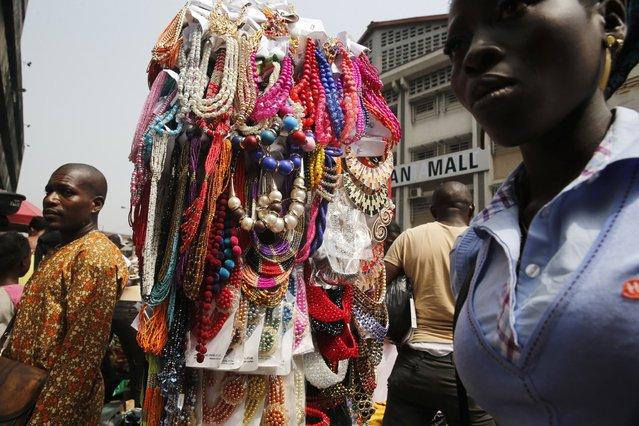Beads and necklaces are displayed for sale at a street side stall at the central business district, a day before Christmas, in Lagos December 24, 2014. (Photo by Akintunde Akinleye/Reuters)