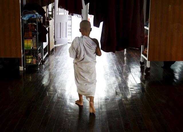 Pre-novice monk Zarnayar, 11-years-old, walks as he studies Buddhist texts at a monastery outside Mandalay, Myanmar, November 10, 2015. (Photo by Olivia Harris/Reuters)