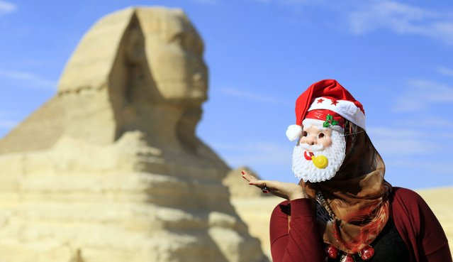A woman wearing a mask of Santa Claus poses for a picture during year-end celebrations in front of the Sphinx at the Giza Pyramids on the outskirts of Cairo December 31, 2014. (Photo by Amr Abdallah Dalsh/Reuters)