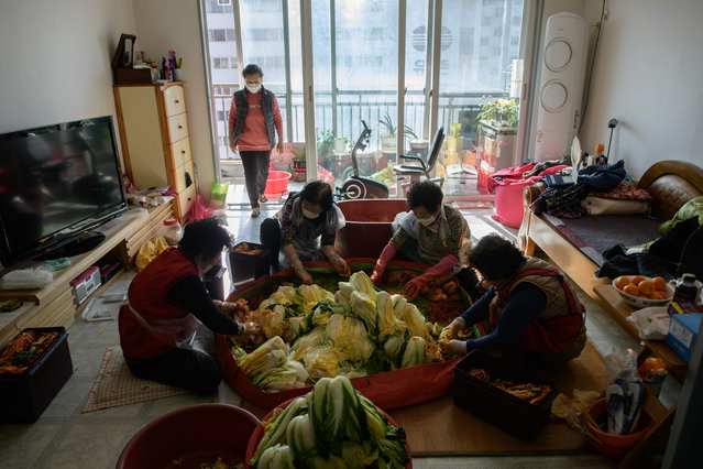 """In photo taken on November 29, 2020 friends of Lee Young-ja make kimchi, a traditional communal process known as """"kimjang"""", at her home in the eastern port city of Donghae. (Photo by Ed Jones/AFP Photo)"""