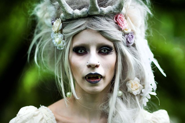 A woman in vampire make-up attends the traditional park picnic on the first day of the annual Wave-Gotik Treffen, or Wave and Goth Festival, in Leipzig, Germany, on May 17, 2013. The four-day festival, in which elaborate fashion is a must, brings together over 20,000 Wave, Goth and steam punk enthusiasts from all over the world for concerts, readings, films, a Middle Ages market and workshops. (Photo by Marco Prosch/Getty Images)