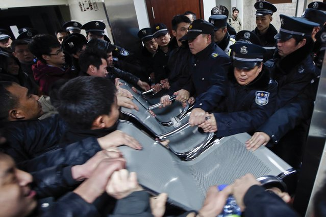 People clash with police as they try to visit relatives injured in a stampede, at a hospital in central Shanghai January 1, 2015. (Photo by Reuters/Stringer)