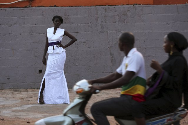 People on a motorcycle ride past model Atou Cisse wearing a bazin outfit made by designer Mariah Bocoum Keita in Bamako, Mali, October 21, 2015. (Photo by Joe Penney/Reuters)