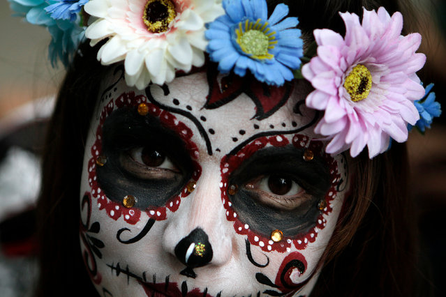 "Girl scout Montso Gomez, 12, dressed as a ""Catrina"", or skeleton lady, waits for the start of the Gran Procession of the Catrinas, to mark the upcoming Day of the Dead holiday, in Mexico City, Sunday, October 23 2016. The gran procession is one of many that will take place in Mexico City as part of the celebrations, culminating with visits to the graves of departed loved ones on Nov. 1 and 2. The figure of a skeleton wearing broad-brimmed hat was first done as a satirical engraving by artist Jose Guadalupe Posada sometime between 1910 and his death in 1913, to poke fun at women who pretended to be European by dressing elegantly and as a critique of social stratification. (Photo by Anita Baca/AP Photo)"