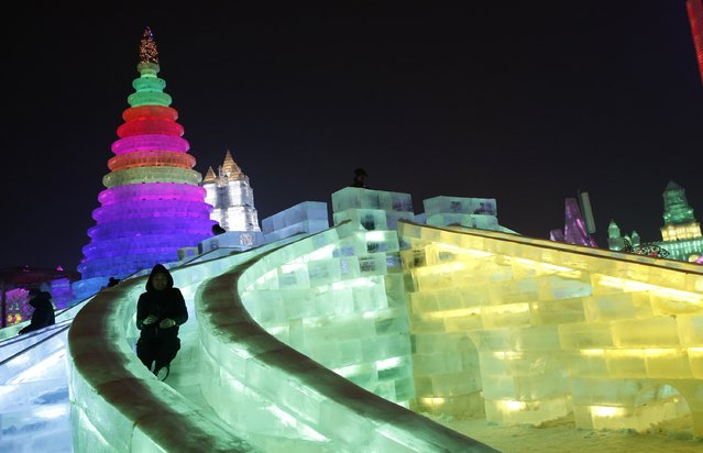 A man rides a slide on an ice sculpture illuminated by coloured lights during a trial operation ahead of the 31st Harbin International Ice and Snow Festival in the northern city of Harbin, Heilongjiang province, January 4, 2015. (Photo by Kim Kyung-Hoon/Reuters)