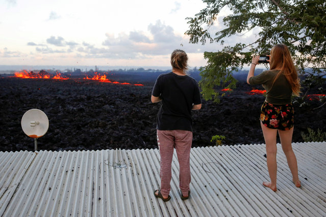 Jolon Clinton, 15, (L), and her sister, Halcy, 17, take photos of a fissure near their home on the outskirts of Pahoa during ongoing eruptions of the Kilauea Volcano in Hawaii, U.S., May 14, 2018. (Photo by Terray Sylvester/Reuters)