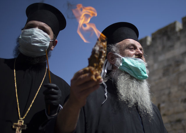 An Orthodox clergyman holds holy fire to transfer to predominantly Orthodox countries from the Church of the Holy Sepulchre, traditionally believed by many Christians to be the site of the crucifixion and burial of Jesus Christ, in Jerusalem's old city after the traditional Holy Fire ceremony was called off amid coronavirus, Saturday, April 18, 2020. A few clergymen on Saturday marked the Holy Fire ceremony as the coronavirus pandemic prevented thousands of Orthodox Christians from participating in one of their most ancient and mysterious rituals at the Jerusalem church marking the site of Jesus' tomb. (Photo by Ariel Schalit/AP Photo)