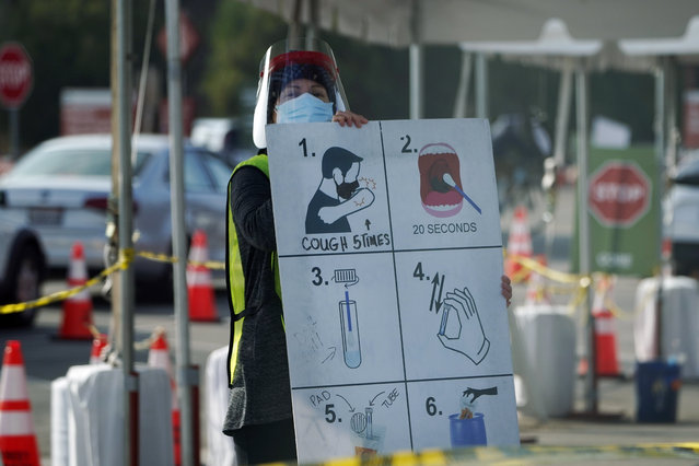 A worker gives instructions to motorists at a COVID-19 testing site Tuesday, January 5, 2021, in Los Angeles. (Photo by Marcio Jose Sanchez/AP Photo)