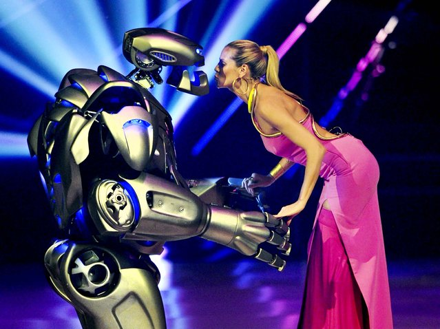 Heidi Klum stands on stage with an actor dressed in a robot costume during the final show of the German television model casting show 'Germany's Next Top model' at the SAP-Arena in Mannheim, Germany, on May 30, 2013. (Photo by Uli Deck/Associated Press)