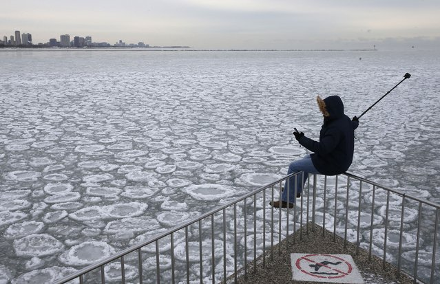 Charles Martinez sits on a railing to take a selfie overlooking the partially frozen Lake Michigan in Chicago, Illinois, January 5, 2015. (Photo by Jim Young/Reuters)