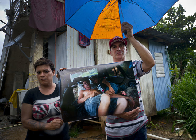 Blanca Rivera and Eduard Rodriguez pose with a printed photo of them that was taken on September 30, 2017 as they slept in their car after their home was destroyed by Hurricane Maria in the San Lorenzo neighborhood of Morovis, Puerto Rico, May 26, 2018. The couple says FEMA rejected their request for financial help to rebuild, so they sold their car to build a room next to his mother's house, behind. (Photo by Ramon Espinosa/AP Photo)