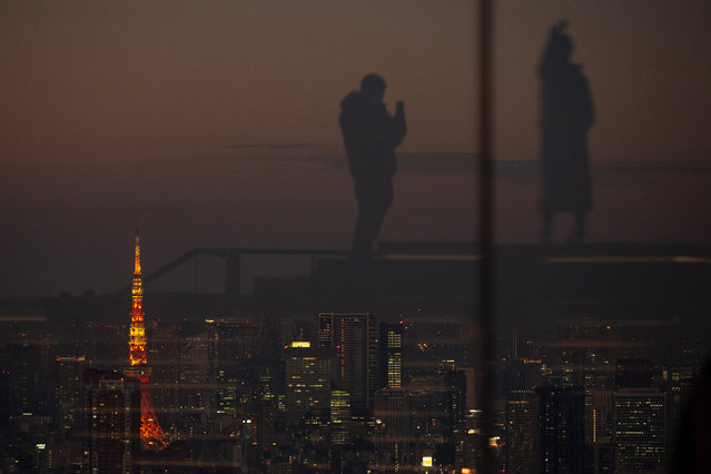 Silhouetted against the warm sunset skyline and the illuminated Tokyo Tower, visitors are reflected on the glass walls of a rooftop observation deck Thursday, January 21, 2021, in Tokyo. (Photo by Kiichiro Sato/AP Photo)