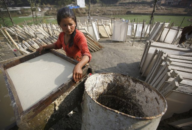 A woman works to create handmade Nepali Lokta paper in Kathmandu January 7, 2015. Lokta papers are made from the fibrous inner bark of Lokta bushes that are found over 5,000 metres above sea level. (Photo by Navesh Chitrakar/Reuters)
