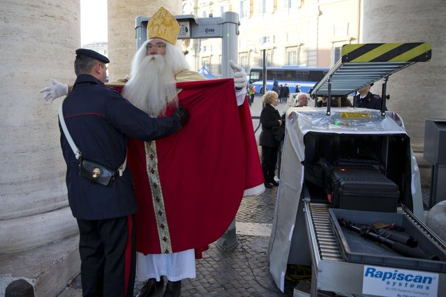 Germany's Wolfgang Kimmig-Liebe, who has been volunteering as Santa Claus for years, is searched by a Carabiniere paramilitary police officer before entering in St. Peter's Square at the Vatican to attend Pope Francis general audience, Wednesday, December 2, 2015. (Photo by Alessandra Tarantino/AP Photo)