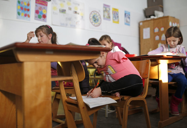 Ramela Meseljevic, a 7 year-old girl born without both of her hands and one of her legs shorter than the other, writes during classes in the her school in Begov Han, Bosnia and Herzegovina December 2, 2015. (Photo by Dado Ruvic/Reuters)