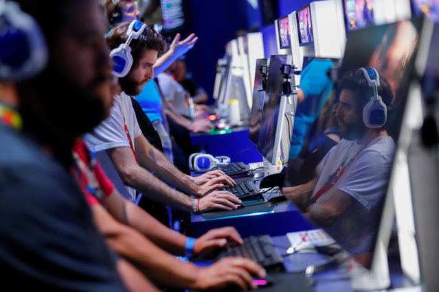 Attendees play video games at E3, the world's largest video game industry convention in Los Angeles, California on June 12, 2018 where hardware manufacturers, software developers and the video game industry present their new games at the 3- day event between June 12-14. (Photo by Mike Blake/Reuters)