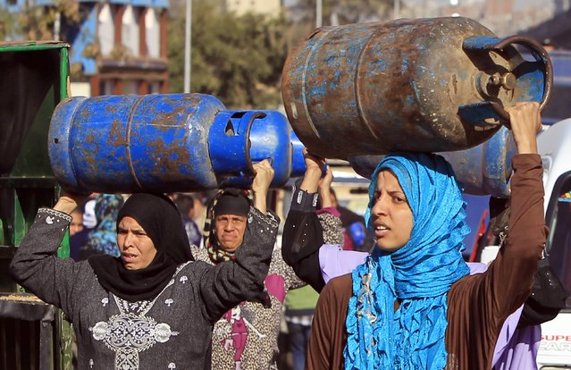 Women carry gas cylinders to be refilled at a distribution point in Cairo January 19, 2015. (Photo by Mohamed Abd El Ghany/Reuters)