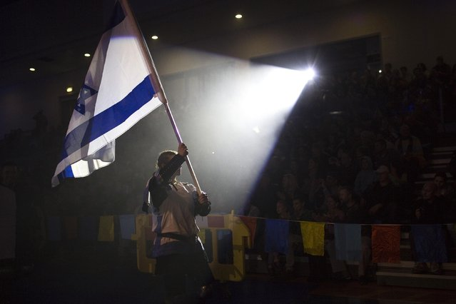 """Ira Rogozovsky from the Israeli team carries the national flag during the """"World Medieval Fighting Championship – the Israeli Challenge"""" in Rishon Letzion near Tel Aviv on January 22, 2015. (Photo by Amir Cohen/Reuters)"""