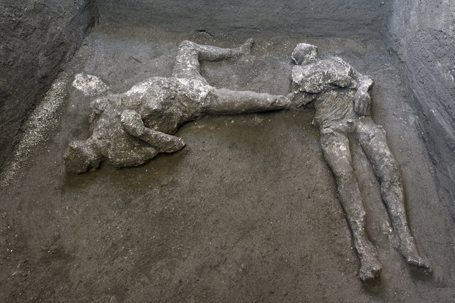 The casts of what are believed to have been a rich man and his male slave fleeing the volcanic eruption of Vesuvius nearly 2,000 years ago, are seen in what was an elegant villa on the outskirts of the ancient Roman city of Pompeii destroyed by the eruption in 79 A.D., where they were discovered during recents excavations, Pompeii archaeological park officials said Saturday, November 21, 2020. (Photo by Parco Archeologico di Pompei via AP Photo)