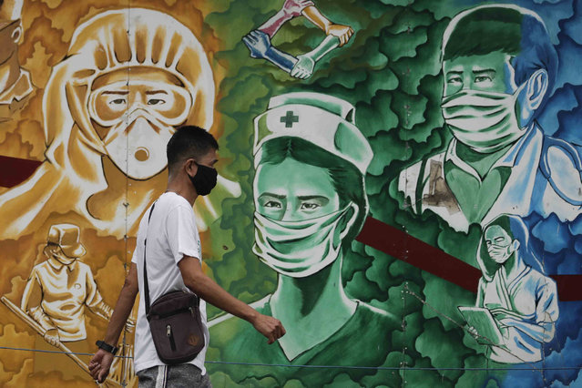 A man wearing a protective mask to prevent the spread of the coronavirus walks beside a mural of health workers outside the Mission Hospital in Pasig, Philippines, Monday, February 22, 2021. Delays have hounded the delivery of COVID-19 to the Philippines, with officials saying the scheduled arrival on Tuesday of 600,000 doses of donated vaccine from Sinovac Biotech Ltd. may be delayed because the China-based firm still lacks an authorization from Manila's Food and Drug Administration for the emergency use of it's vaccine. (Photo by Aaron Favila/AP Photo)