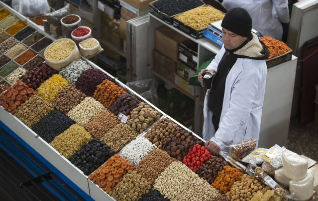 A vendor sells fruits and nuts at the Green Bazaar in Almaty January 23, 2015. Kazakhstan is spending billions of dollars of its reserves to keep devaluation of its currency gradual and reduce inflationary risks of the sort thrown up in Russia by the rouble's slide, analysts and former central bank officials say. (Photo by Shamil Zhumatov/Reuters)