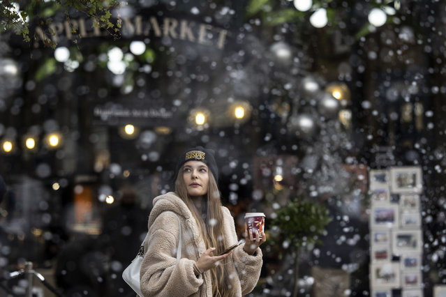 """A member of the public walks through fake snow in Covent Garden on December 16, 2020 in London, England. In """"Tier 3"""" of England's pandemic-control measures, restaurants and pubs will be limited to takeaway and delivery, although shops are allowed to remain open. (Photo by Dan Kitwood/Getty Images)"""