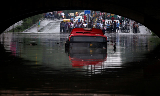 A bus is seen submerged on a flooded road under a railway bridge after heavy rains in New Delhi, India, July 13, 2018. (Photo by Adnan Abidi/Reuters)