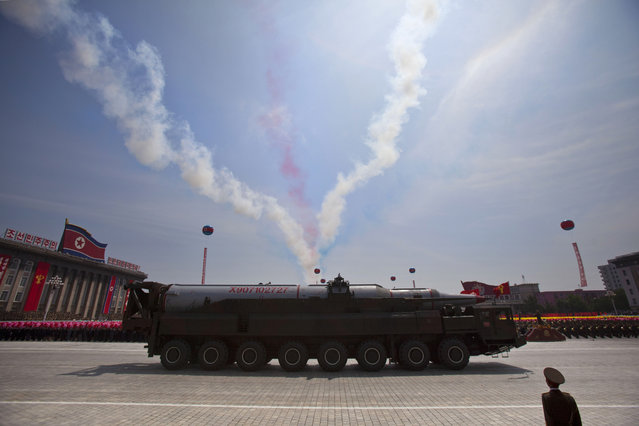 A North Korean missile rolls by as colored smoke trails, left by flying aircraft, streak the sky during a mass military parade on Kim Il Sung Square in Pyongyang to mark the 60th anniversary of the Korean War armistice Saturday, July 27, 2013. (Photo by David Guttenfelder/AP Photo)