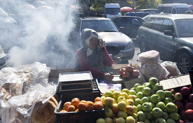 A seller waits for customers at a street market in Bishkek, Kyrgyzstan, Monday, October 12, 2020. Kyrgyzstan's president on Monday ordered a new, week-long state of emergency in the country's capital after parliament failed to consider and approve his previous order within the legally required three days. (Photo by Vladimir Voronin/AP Photo)