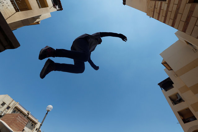 """Zeinab Helal from Parkour Egypt """"PKE"""" practices her parkour skills around buildings on the outskirts of Cairo, Egypt on July 20, 2018. (Photo by Amr Abdallah Dalsh/Reuters)"""