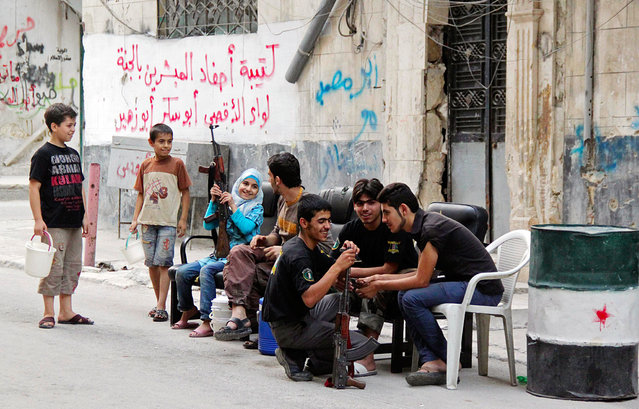 A girl sitting with Syrian Army fighters holds up a gun, along a street in Aleppo August 1, 2013. (Photo by Loubna Mrie/Reuters)