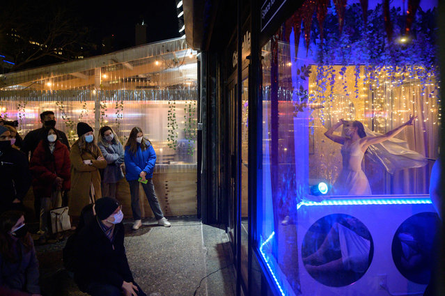 Audience members watch as performers stage a free production of Romeo and Juliet in a vacant shop window on a west side street in Manhattan, New York, on March 13, 2021. The production, by The Love Show theatre company, was part of a run of performances using a vacant shop window as an answer to the limitations faced by performers following the shutdown of theatre venues during the covid-19 novel coronavirus pandemic. (Photo by Ed Jones/AFP Photo)