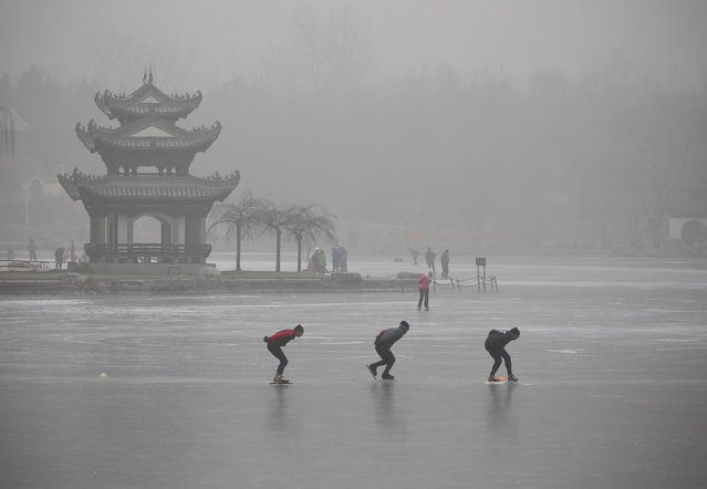 People skate on a lake at Taoranting Park during a hazy day, in Beijing, China, December 26, 2015. (Photo by Reuters/Stringer)