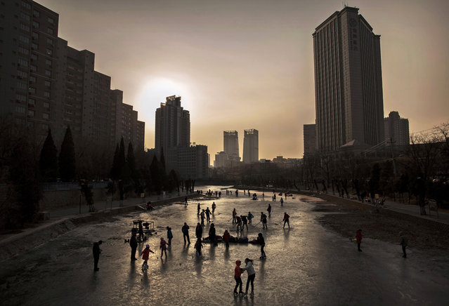 Skaters exercise and play ice hockey on a frozen canal on February 3, 2015 in Beijing, China. The Chinese capital is a candidate city for the 2022 Winter Olympics. (Photo by Kevin Frayer/Getty Images)