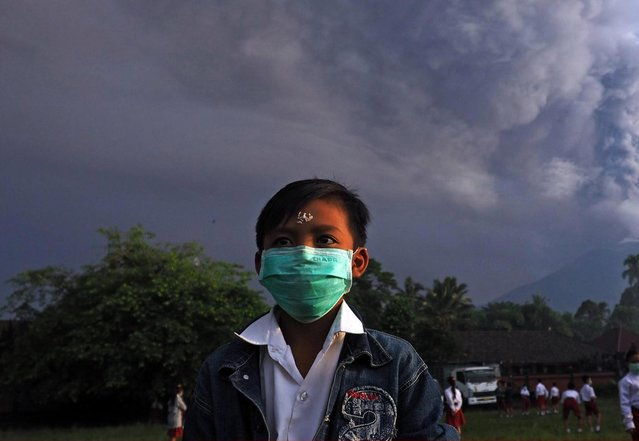 An elementary school student with a face mask is seen in a school ground before school in Rendang village of Karangasem, Bali, Indonesia on November 28, 2017. Until today, the students are still in school as usual, even though the government increased the volcano alert to highest level in 7 kilometer radius range of Mount Agung and extend the closure of I Gusti Ngurah Rai International Airport, Bali. (Photo by Mahendra Moonstar/Anadolu Agency/Getty Images)