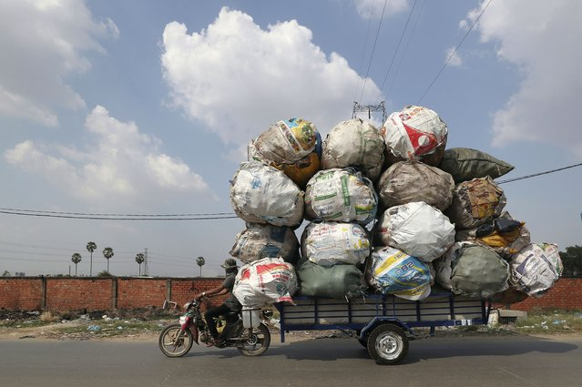 A biker carrying huge bags of recyclables travels on a street outside Phnom Penh, Cambodia on Saturday, March 27, 2021. (Photo by Heng Sinith/AP Photo)