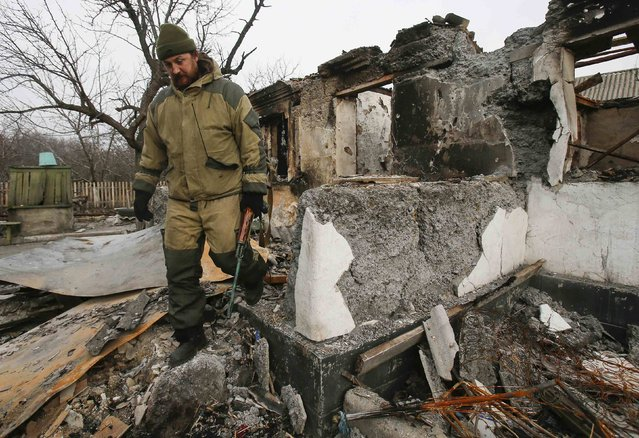 A member of a rebel unit of the self-proclaimed separatist Donetsk People's Republic walks past a house destroyed by shelling in the village of Olenivka, south of Donetsk, February 7, 2015. (Photo by Maxim Shemetov/Reuters)