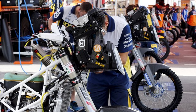 Mechanics of the Husqvarna Racing Team work in the team's box ahead of the Dakar Rally 2016 in Buenos Aires, Argentina, December 31, 2015. (Photo by Marcos Brindicci/Reuters)