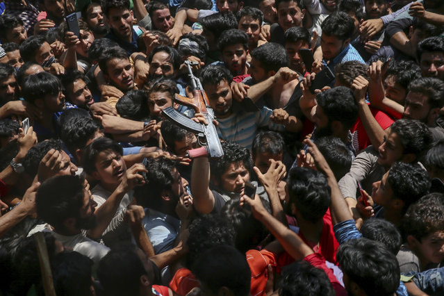 Kashmiri villagers stretch out their hands to touch a Pakistani rebel, as a mark of respect, as he arrives at a funeral to pay tributes to slain rebels Umar Malik and Wakar Sheikh in Malikgund village, south of Srinagar, Indian controlled Kashmir, August 4, 2018. At least seven rebels and an Indian army soldier were killed in gunbattles in disputed Kashmir, triggering violent protests by residents opposed to Indian rule, officials said Saturday. (Photo by Dar Yasin/AP Photo)