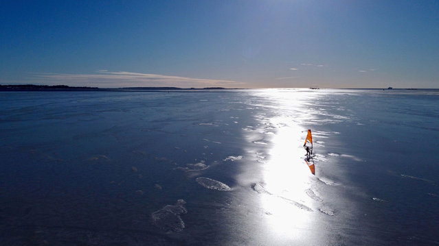 An aerial photo taken on February 28, 2021 shows an ice surfer skating across the frozen Baltic Sea off the coast of Helsinki. What to do if you are a windsurfing enthusiast in a country where the sea freezes over for months of the year? For a group of Finns, the answer is to kit out sailboards with skates and take to the ice, reaching speeds of up to 100km/h (62mph) in a burgeoning sport that can only be practised in a handful of places around the world. (Photo by Sam Kingsley/AFP Photo)