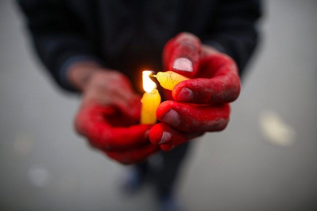 A child at a home for HIV-affected children and women and victims of trafficking attends a candlelight prayer meeting for those who have lost their lives to AIDS on the eve of World AIDS Day in Kathmandu, Nepal, November 30, 2016. (Photo by Narendra Shrestha/EPA)