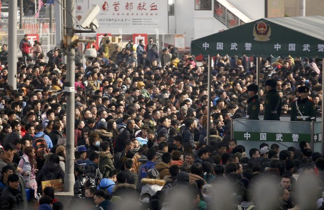 Passengers stand on lines to enter platforms while paramilitary policemen stand guards at a railway station in Beijing February 16, 2015. (Photo by Kim Kyung-Hoon/Reuters)
