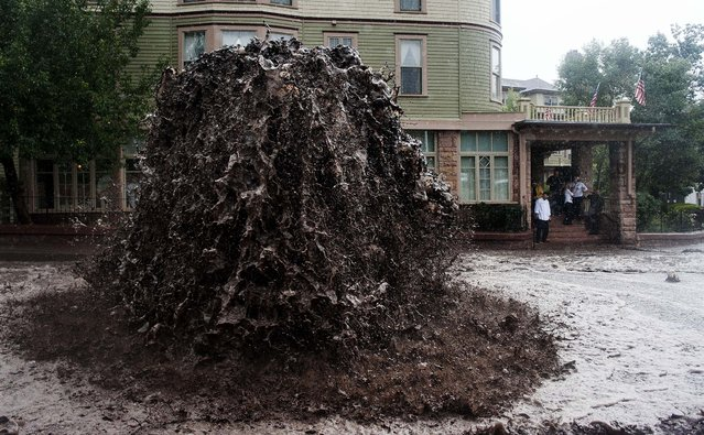 """A geyser of floodwater shoots out of a sewer in Manitou Springs, Colorado, on September 12, 2013. The National Weather Service warned of an """"extremely dangerous and life-threatening situation"""" throughout the region; at least three people have died as a result of the flooding. (Photo by Michael Ciaglo/The Gazette)"""