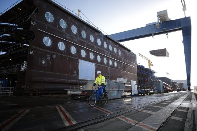 A ship builder cycles past a section of the Oasis Class 3 cruise ship under construction at the STX Les Chantiers de l'Atlantique shipyard site in Saint-Nazaire, western France, February 17, 2015. (Photo by Stephane Mahe/Reuters)
